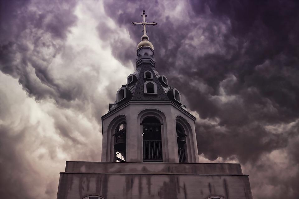 На фото изображена церковь на фоне черных туч.