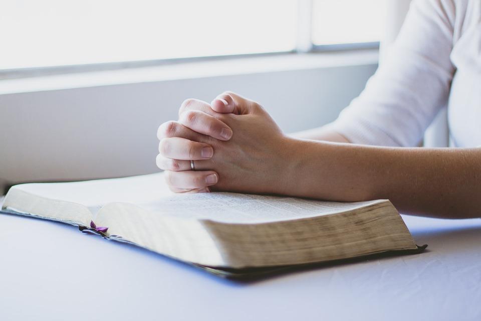 На фото изображена женщина, которая сложила руки на Библию.