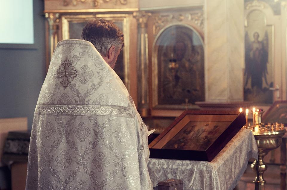 На фото изображен священник, молящийся над иконами в храме.