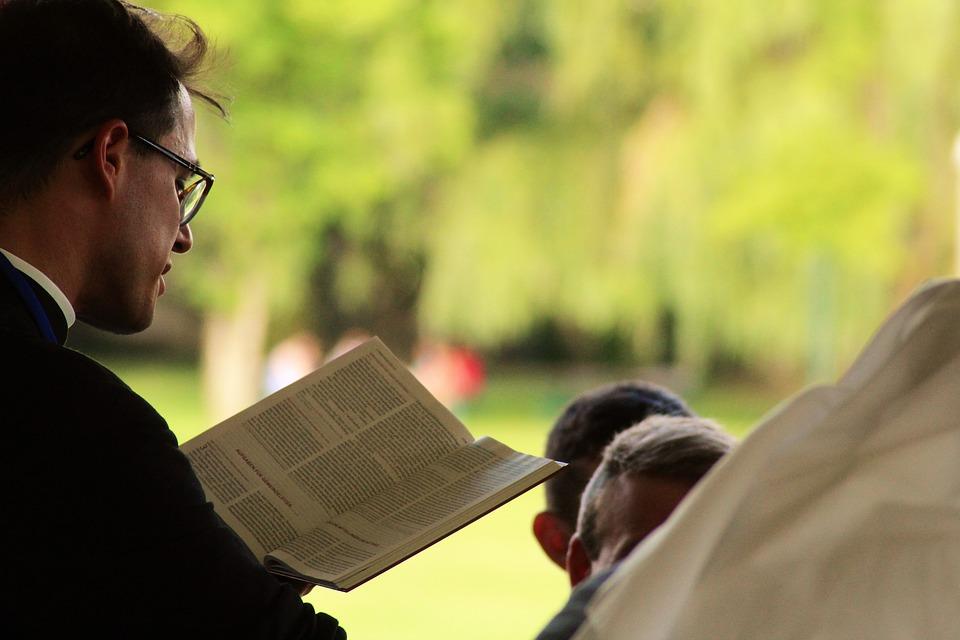На фото священник читает книгу.