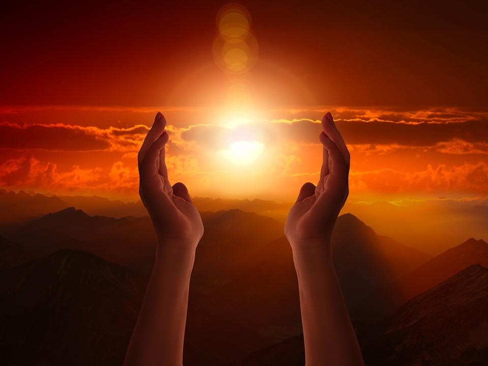 На фото изображены руки, поднятые вверх на фоне заката.