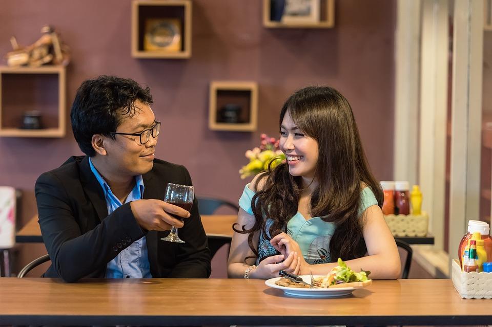 На фото изображена флиртующая парочка, сидящая в кафе.