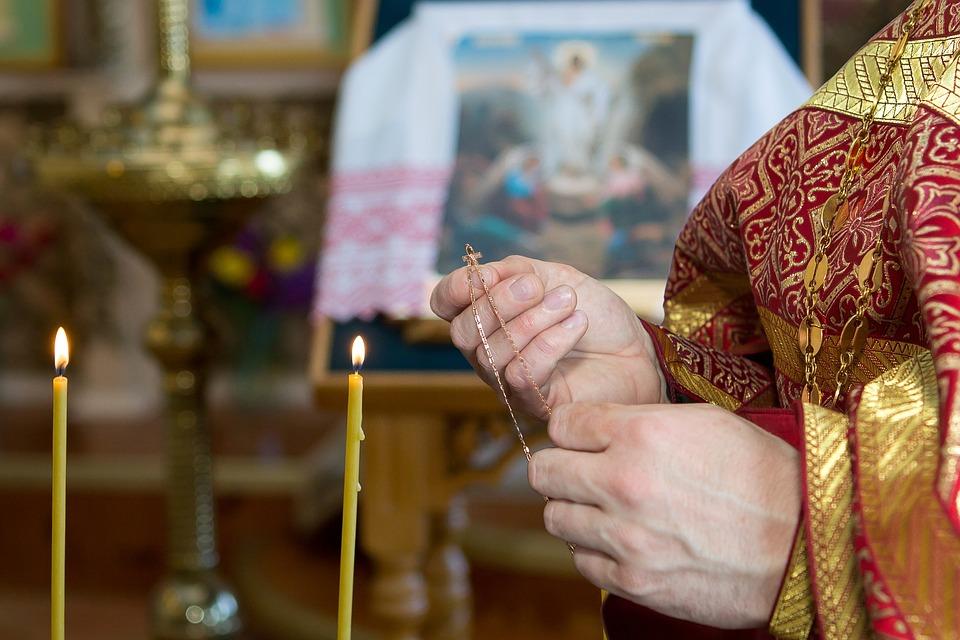 На фото изображен священник, который держит золотой нательный крестик в руках.