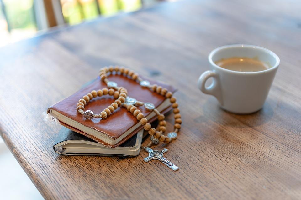 На фото изображена Библия, крестик и чашка кофе.