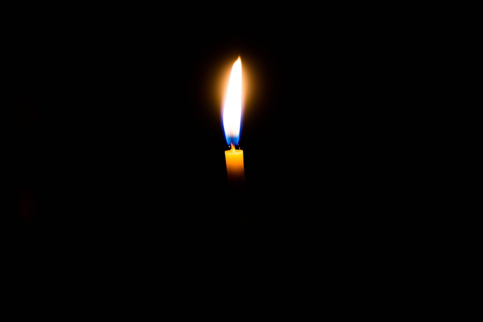 На фото изображена горящая свеча на черном фоне.