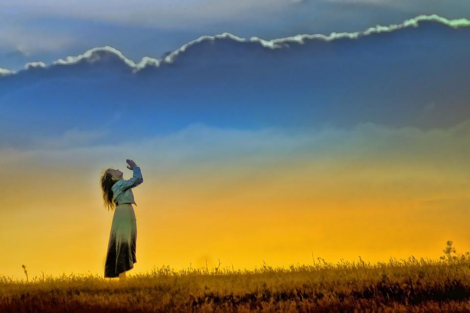 На фото женщина в поле, которая молиться Господу.