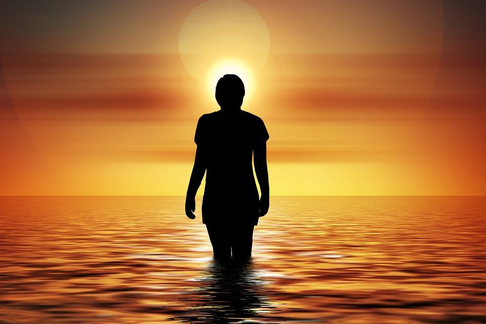 На фото девушка в воде на фоне заката.