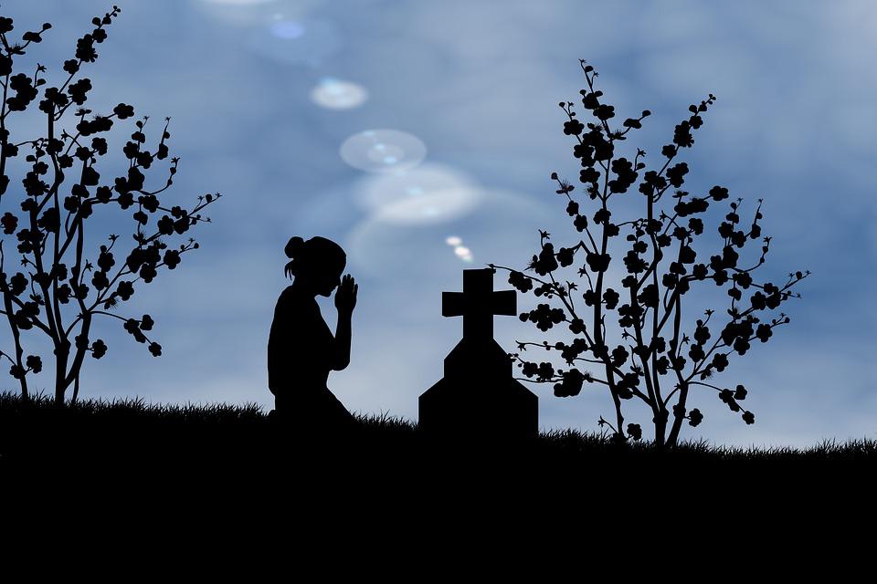 На фото девушка молиться кресту.