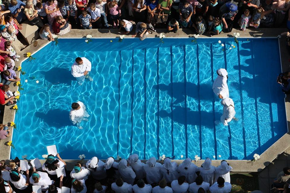 На фото изображение обряда крещения. Бабтисты стоят в воде.