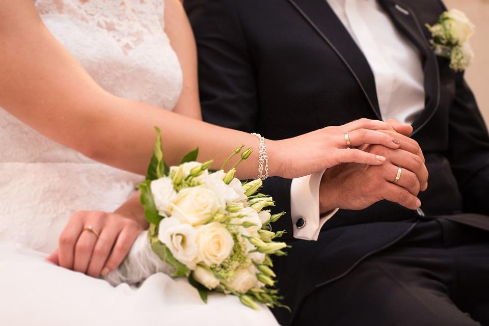 На фото изображена женщина и мужчина, на руках у которых обручальные кольца.