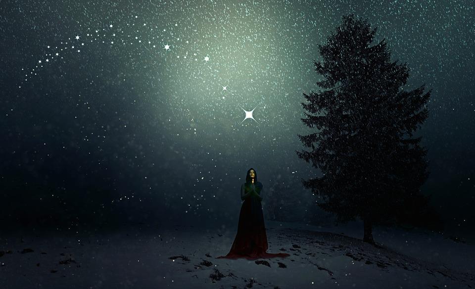 На фото изображена женина, которая стоит зимой в снегопад и молиться Господу, держа свечку в руках.