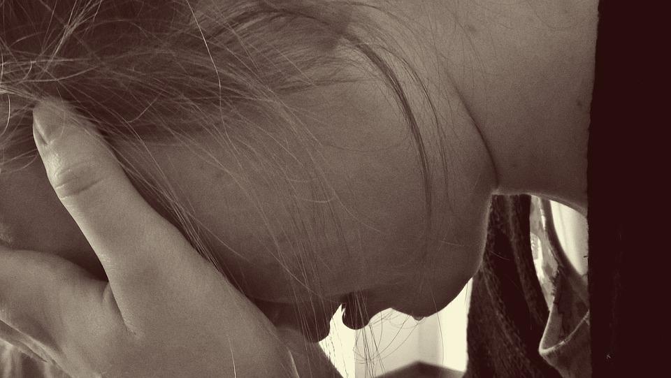 На фото изображена девушка, которая плачет.