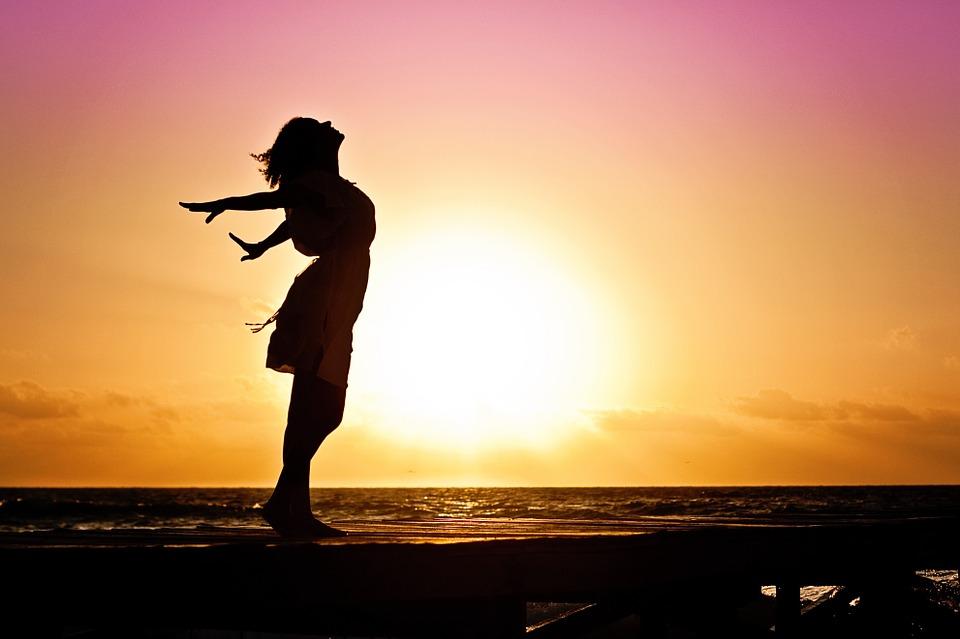 На фото изображена счастливая девушка на фоне восхода солнца.