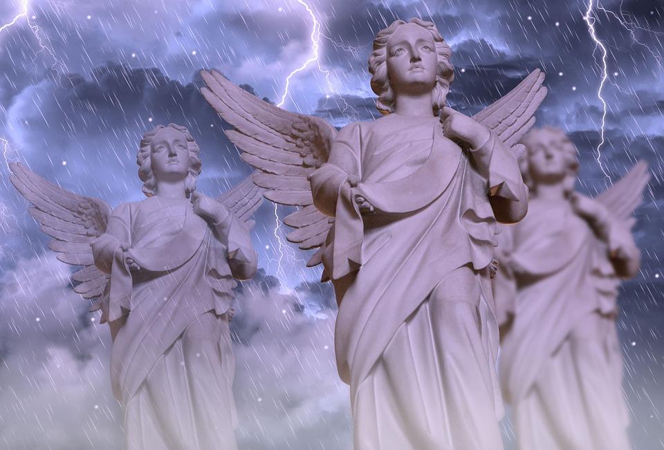 На фото изображено три ангела под грозой и дождем.