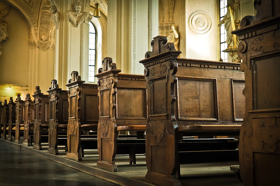 На фото изображены деревянные скамейки внутри храма.