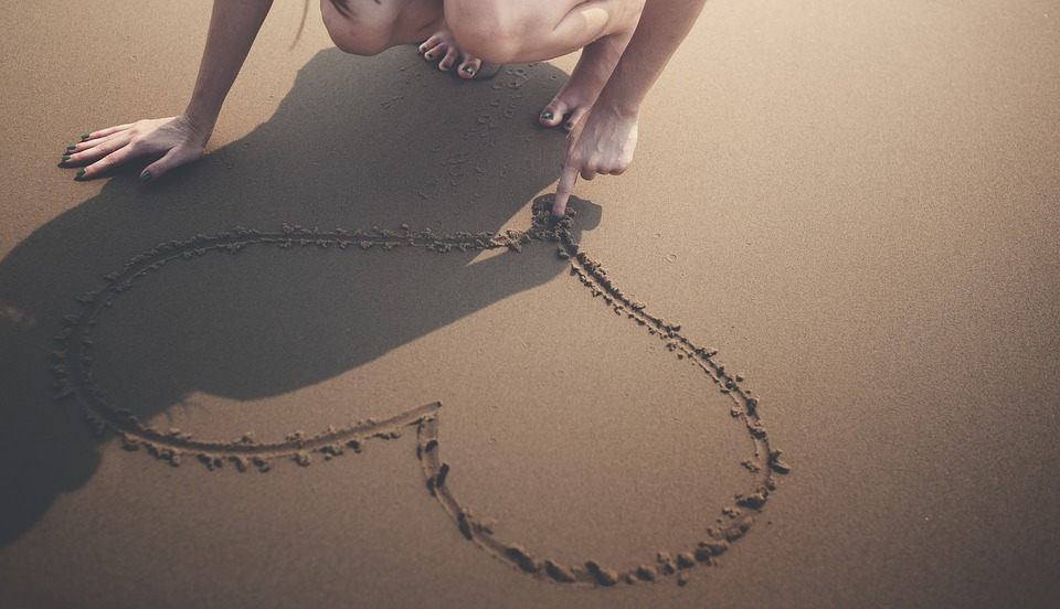 На фото девушка на песке рисует пальцем сердце.