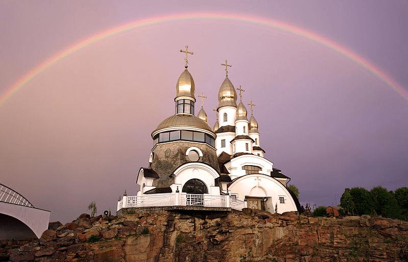 На фото изображена радуга над церковью.