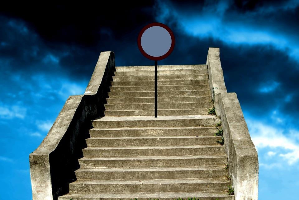 На фото бетонная лестница со знаком, которая ведет в небо.