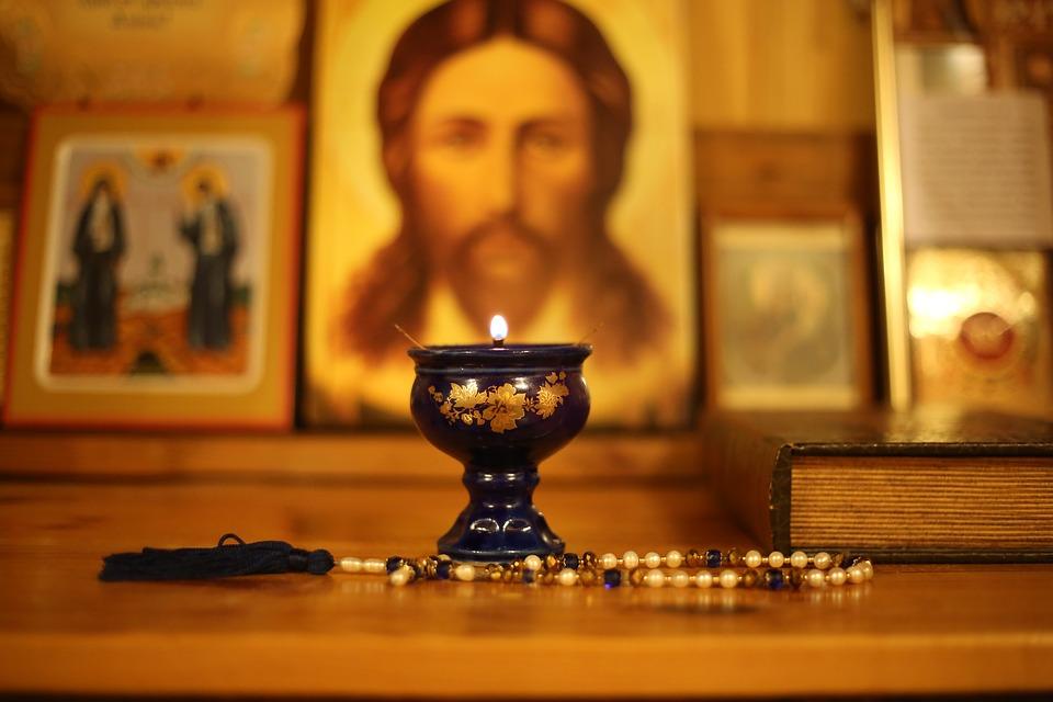 На фото изображена зажженная лампада на фоне икон.