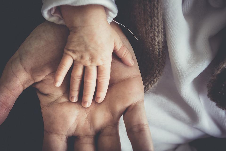 На фото изображена ладошка взрослого, и рука малыша.