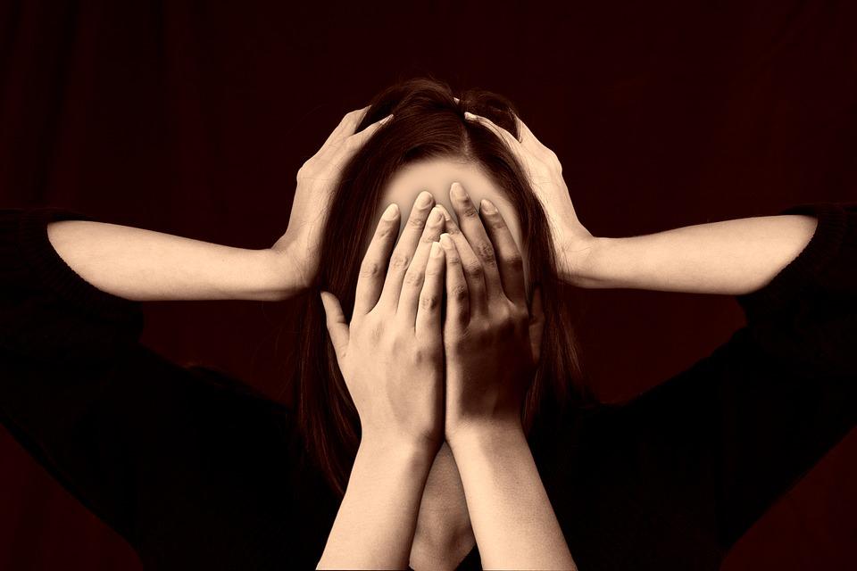 На фото изображена женщина, которая закрывает уши и лицо руками.