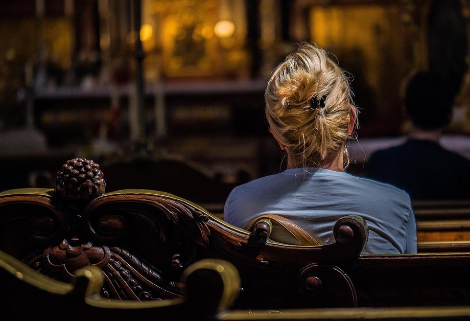 На фото женщина молится в храме.