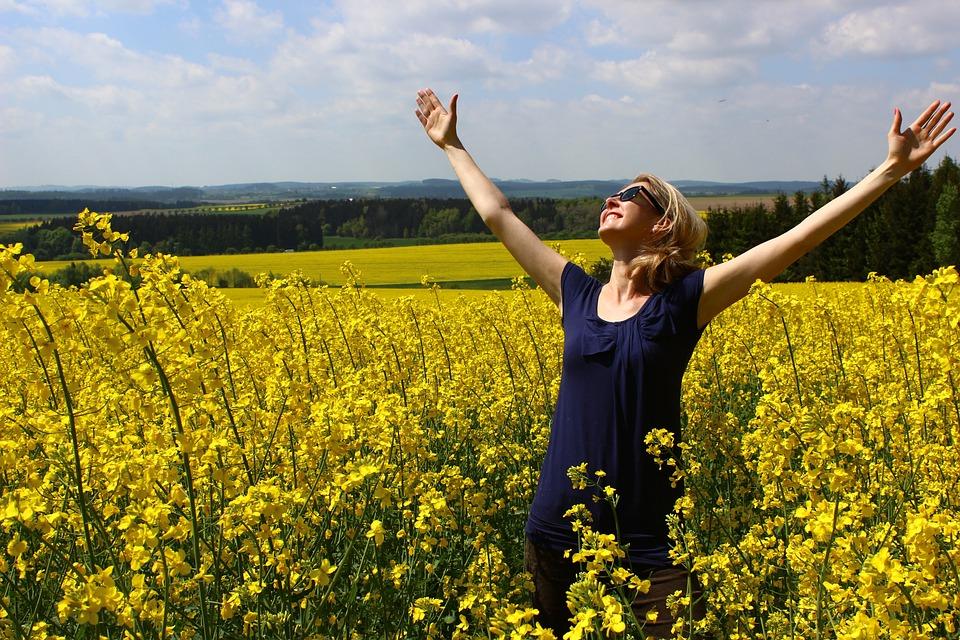 На фото счастливая девушка, улыбающаяся небесам.