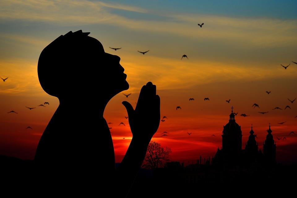 На фото изображен силуэт молящегося мальчика на фоне заката.