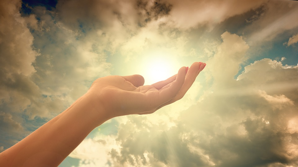 На фото изображена рука молящего на фоне неба
