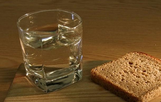 На фото изображен стакан с водой и черный хлеб.
