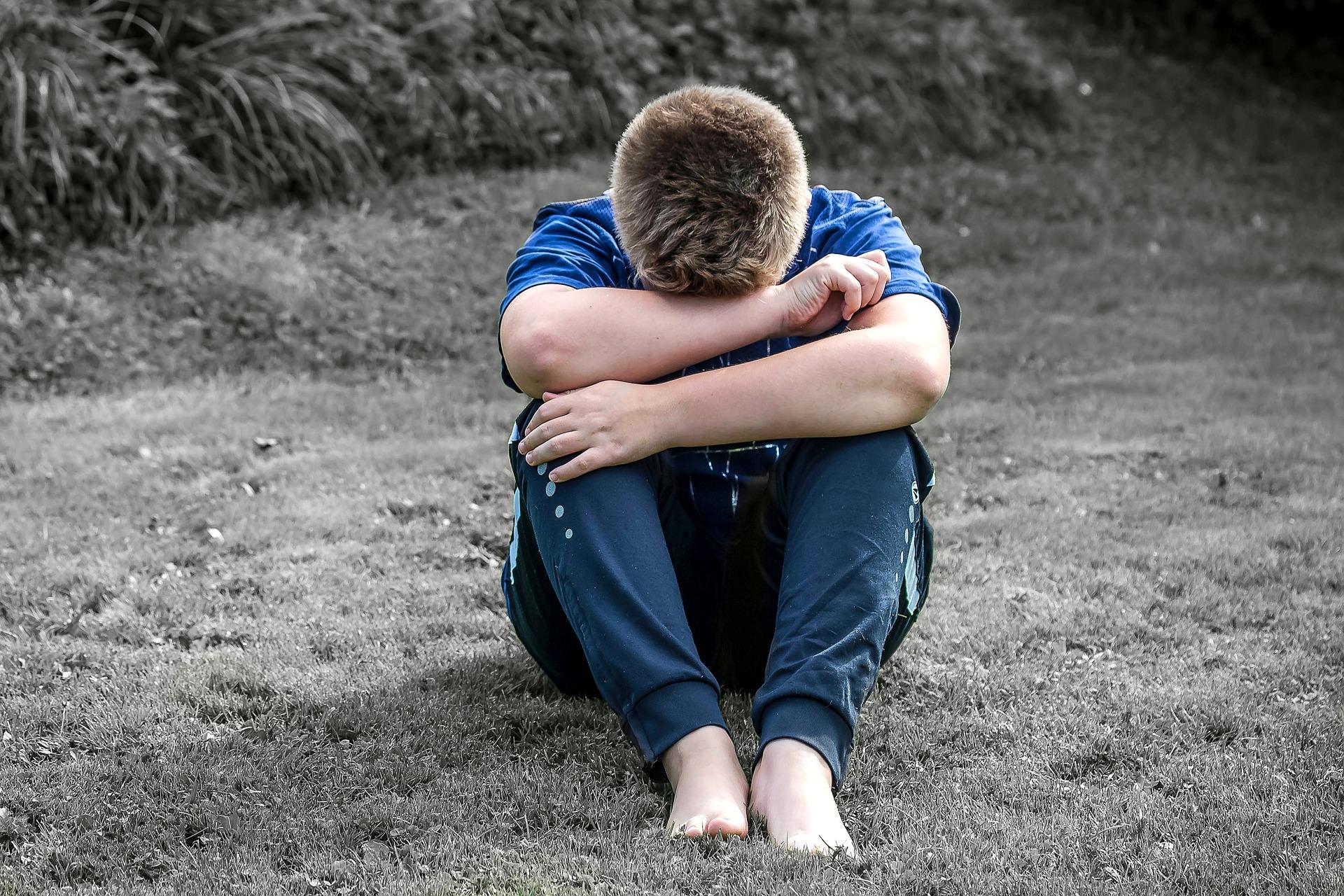 На фото изображен парень, который грустит.