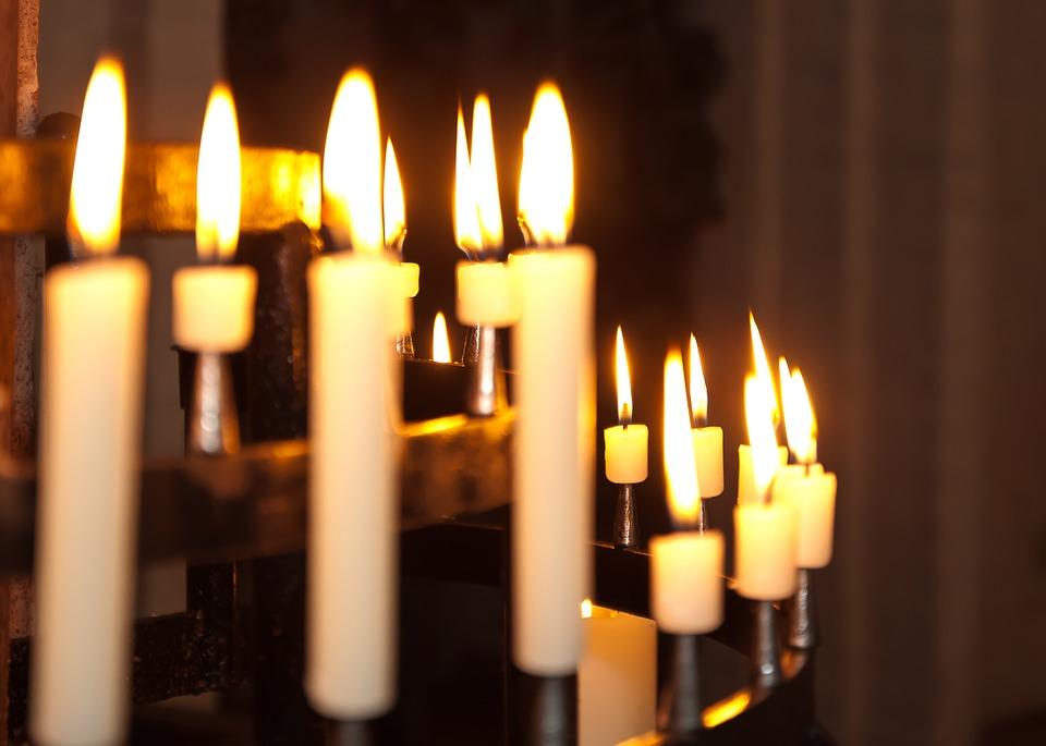 На фото изображены свечи, горящие в церкви.