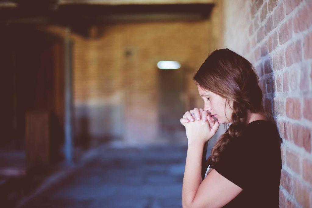 На фото изображена девочка во время молитвы