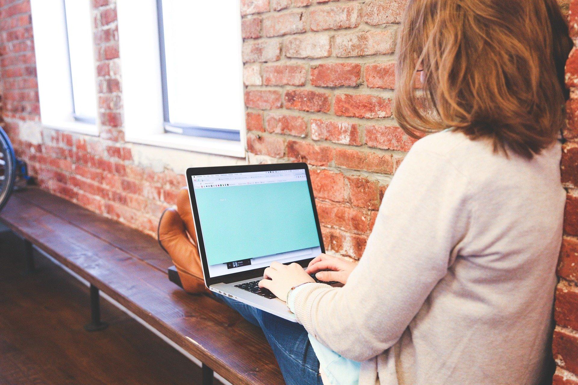 На изображении девушка сидит за ноутбуком и что-то печатает.