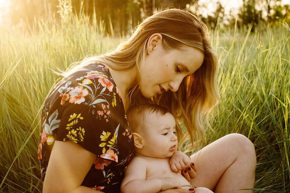 На фото изображена мама с ребенком, сидящие в траве.
