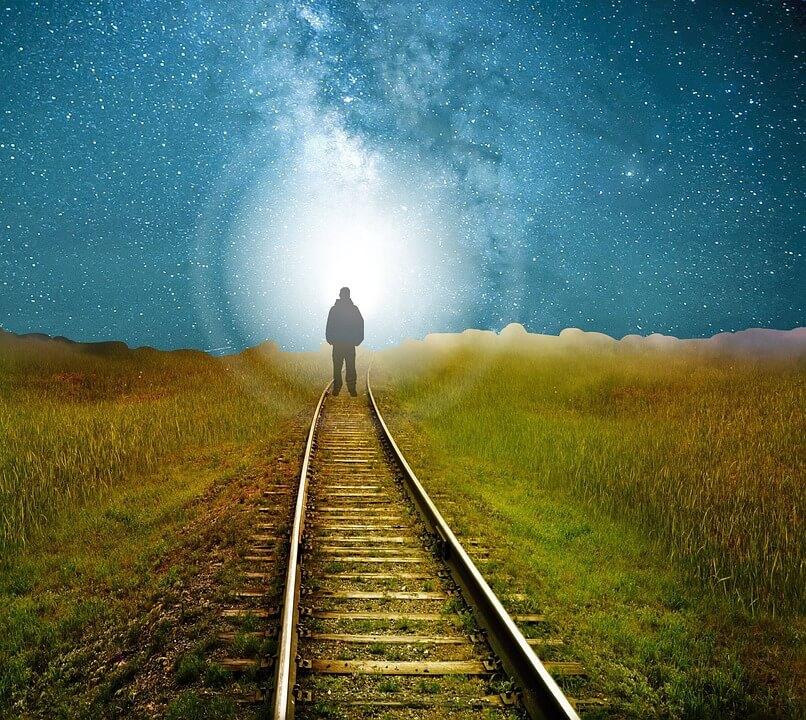На фото изображена уходящая человеческая тень на железной дороге.