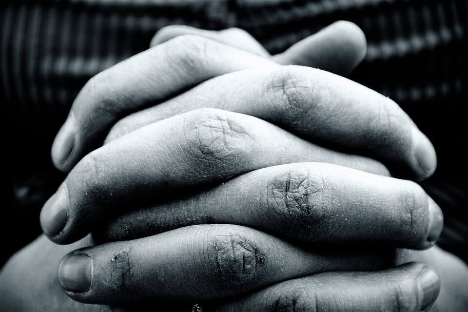 На фото изображены руки молящегося человека.