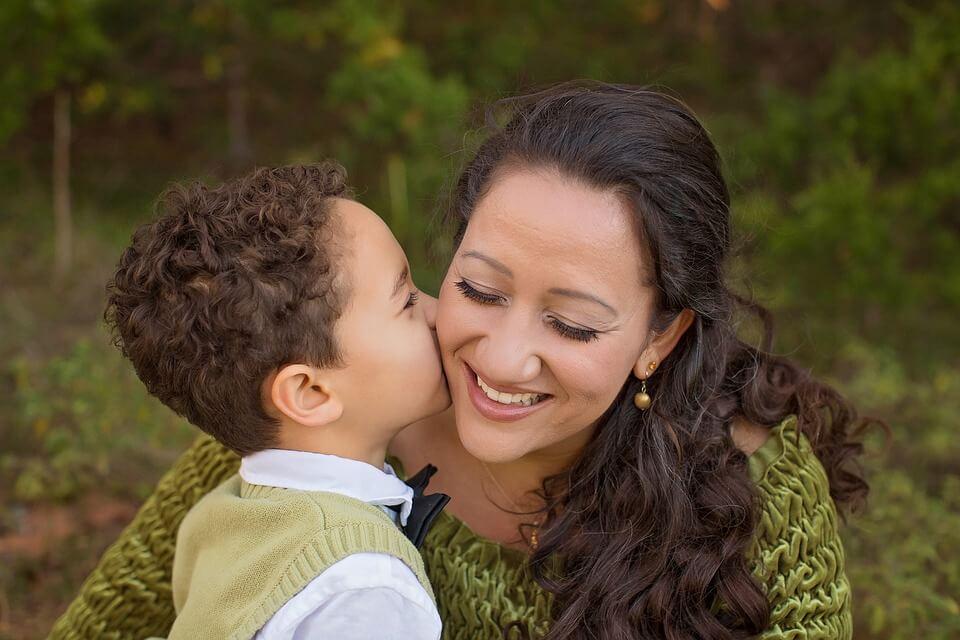 На фото изображ мальчик, который целует маму в щеку.