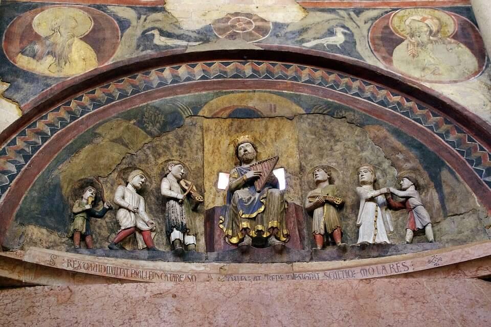 На фото изображен царь Давид и люди вокруг него, играющие на музыкальных инструментах.