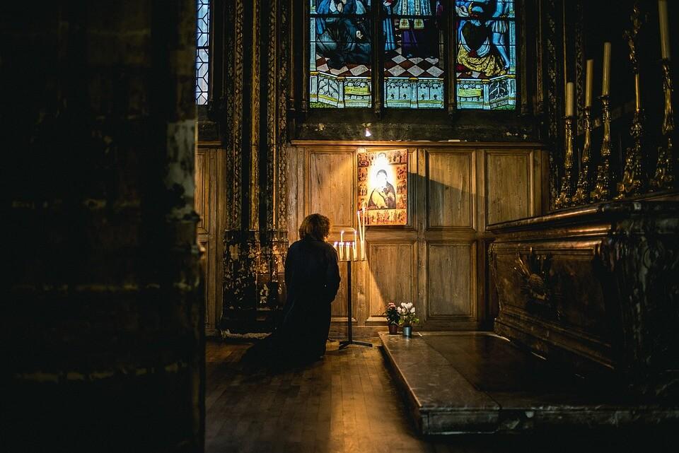 На фото изображен молящийся на коленях пред иконой.