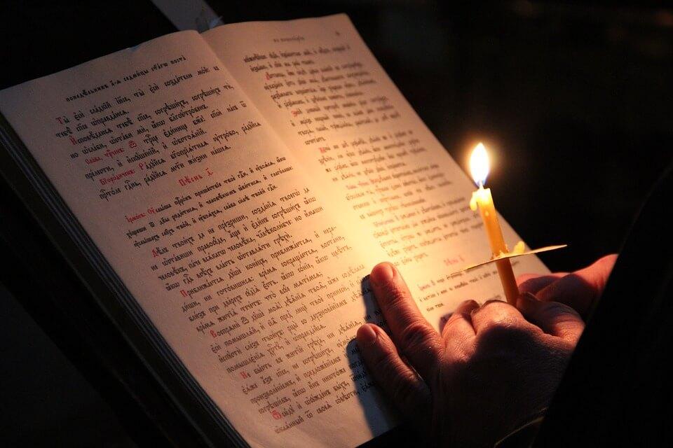 На фото изображен открытый молитвослов и горящая свеча.
