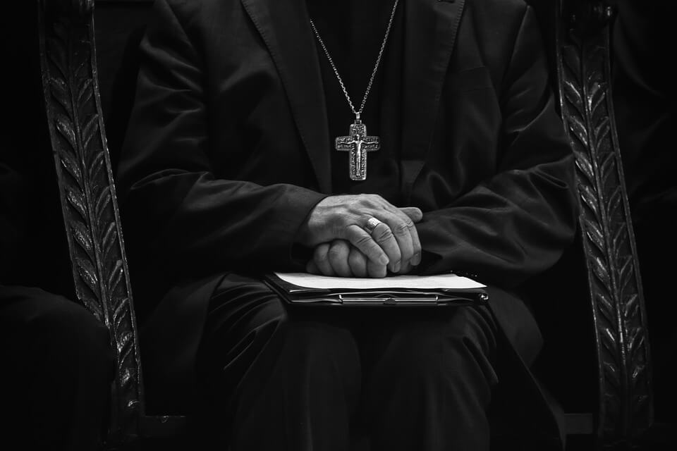 На фото изображен епископ, который сидит сложа руки.
