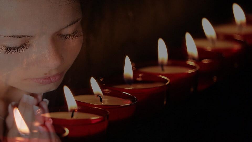 На фото изображена девушка и горящие свечи.