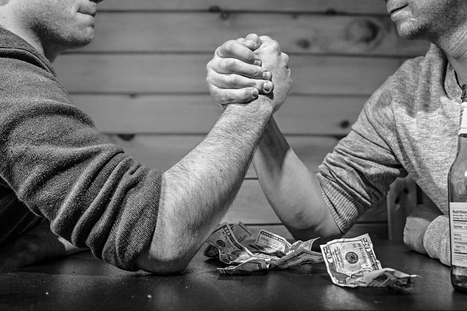 На фото изображено, как двое мужчин борются на руках.