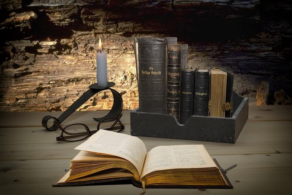 На фото изображены открытая священная книга, горящая свеча и книги в ящике.