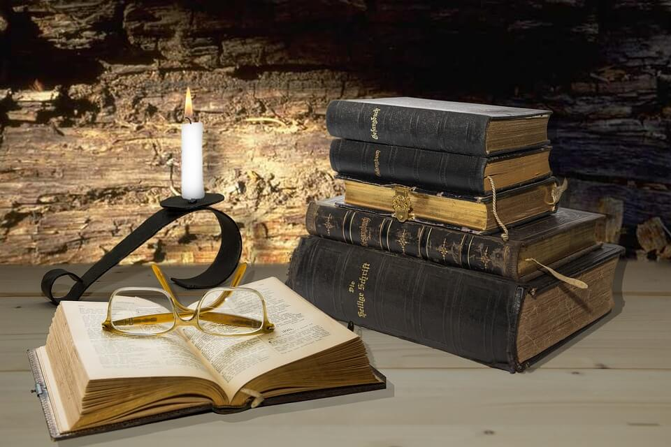 На фото изображен открытый псалтырь, горящая свеча и стопка книг.