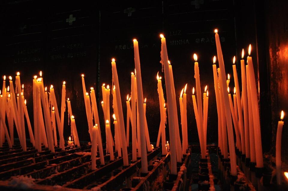 На фото изображено множество горящих свечей.