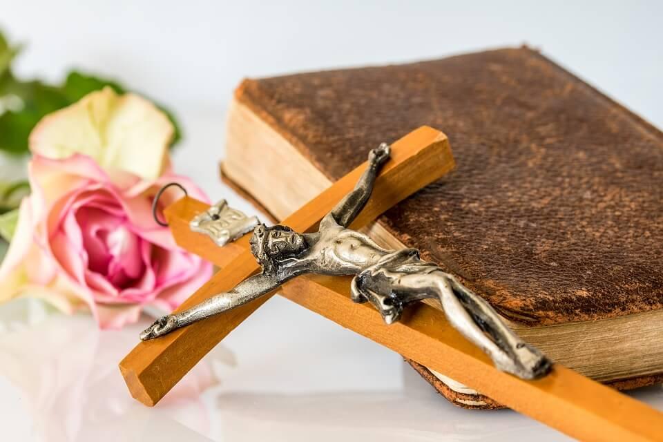 На фото изображены крест с распятием и книга, которые лежат на столе.