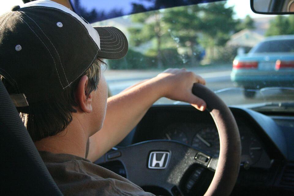 На фото изображен парень за рулем машины.