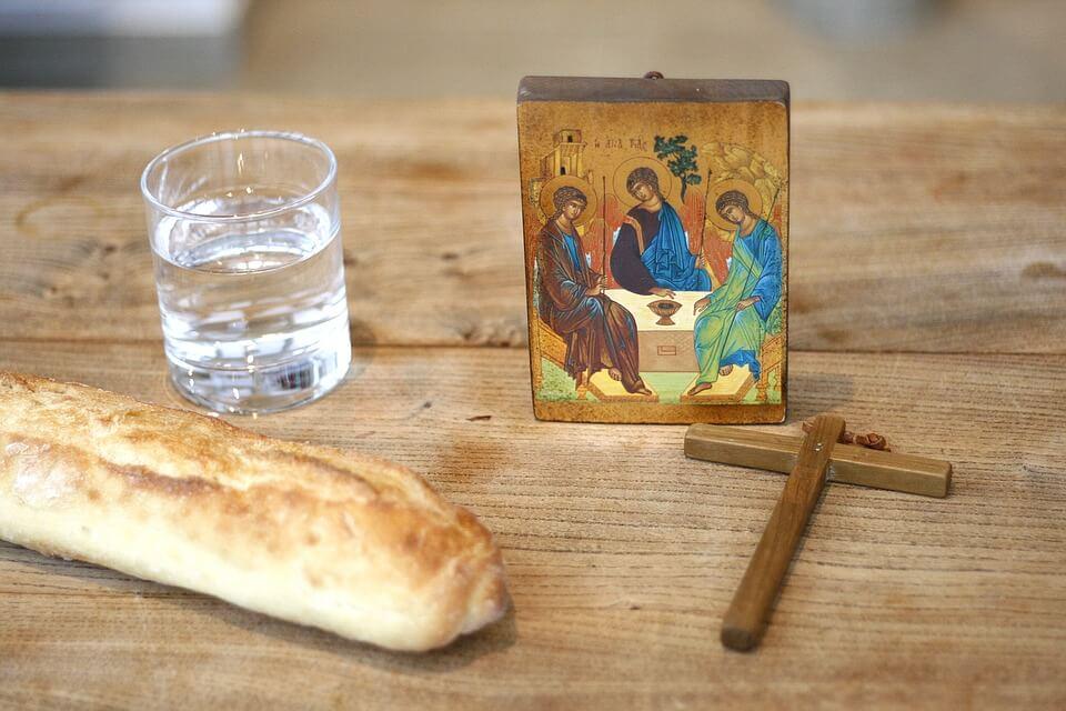 На фото изображены крест, икона, хлеб и стакан с водой, стоящие на столе.